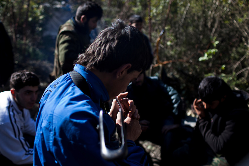 A young fighter from the Free Syrian Army lights a cigarette beside a fire at a rebel campsite in North-West Syria, near the Turkish border, March 3, 2012. Photo: ED GILES.