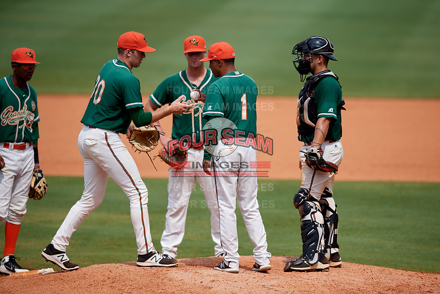 Greensboro Grasshoppers coach Angel Espada (1) hands the ball to relief pitcher Travis Neubeck (30) as second baseman Jose Devers (2), first baseman Micah Brown (10), and catcher Michael Hernandez (17) look on during a game against the Lakewood BlueClaws on June 10, 2018 at First National Bank Field in Greensboro, North Carolina.  Lakewood defeated Greensboro 2-0.  (Mike Janes/Four Seam Images)