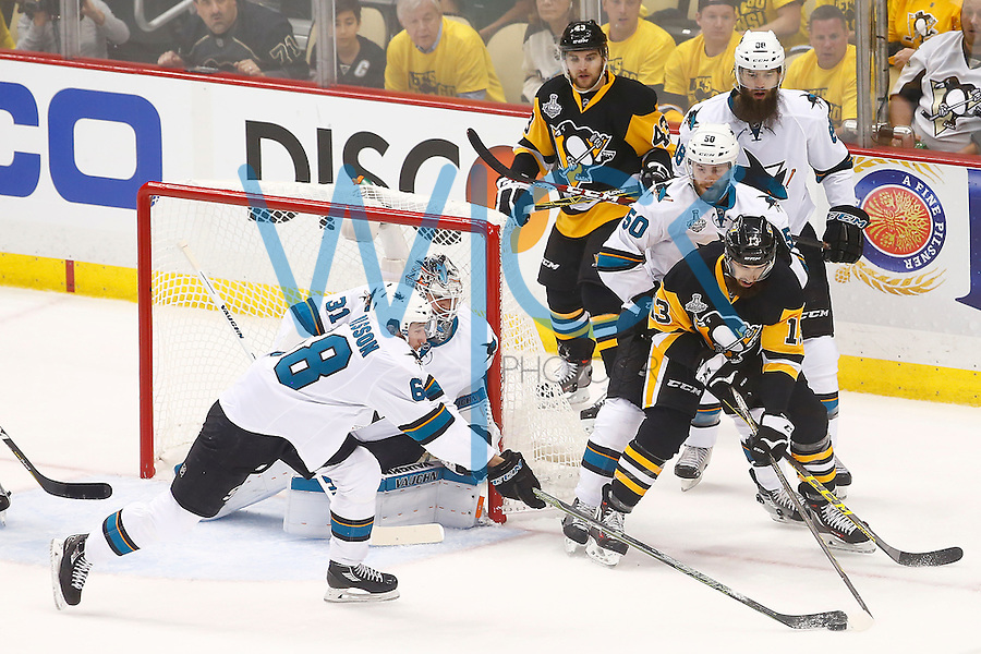 Nick Bonino #13 of the Pittsburgh Penguins attempts to find the puck in front of Melker Karlsson #68 of the San Jose Sharks in the first period during game one of the Stanley Cup Final at Consol Energy Center in Pittsburgh, Pennslyvania on May 30, 2016. (Photo by Jared Wickerham / DKPS)