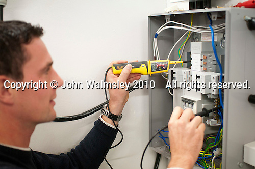 Student electrician using a multimeter to test a circuit, Able Skills, Dartford, Kent.