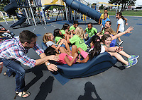 NWA Democrat-Gazette/ANDY SHUPE<br /> Zachary Steen (left), a teaching intern from the University of Arkansas teaching at Jones Elementary School in Springdale, spins a merry-go-round as Jadeh Roberts, 10, (right) a fifth-grader at Jones, laughs Thursday, Sept. 10, 2015, during a dedication ceremony for the Kiwanis International Centennial Playground at the renovated Luther George Grove Street Park in Springdale. The playground comes as a part of Kiwanis' national effort to build playgrounds to mark the organization's 100-year anniversary.