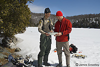 Government wildlife enforcement official checking on ice fishermen in winter