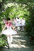 Girls dressed as fairies walk down a rose covered pathway in dappled sunlight