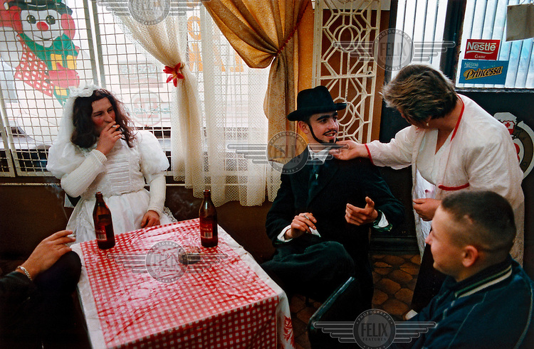 "The Bride and the Jew relax in a local bar. The ""Decapitation of Death"" takes place in the small town of Jedlinsk, in central Poland, every year on the Tuesday before Lent (Shrove Tuesday). Its exact origins are unclear, but it is believed to have begun in the 16th Century, and was first written by the local rector in 1839. The whole town gets involved in the theatrical pageant, and the words uttered by the main players, the Bride, Angel, Jew, Hangman, Devil and Bartholomew the Policeman, are well known among locals. It is believed that on this day Death gets drunk and loses its scythe, offering the perfect opportunity for him to be arrested and executed. After calls from the crowd, Death is sentenced to death, and a grand feast, marking the beginning of Lent, can begin."