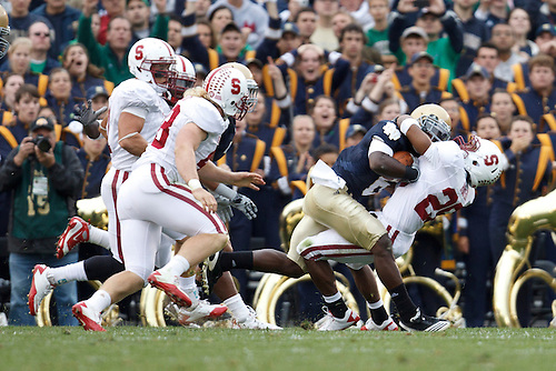 Stanford safety Delano Howell (#26) tackles Notre Dame wide receiver Theo Riddick (#6) during NCAA football game between Stanford and Notre Dame.  The Stanford Cardinal defeated the Notre Dame Fighting Irish 37-14 in game at Notre Dame Stadium in South Bend, Indiana.