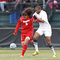 University of New Mexico forward Devon Sandoval (9) on the attack as University of Connecticut defender Sergio Campbell (4) defends..NCAA Tournament. With a goal in the second overtime, University of Connecticut (white) defeated University of New Mexico (red), 2-1, at Morrone Stadium at University of Connecticut on November 25, 2012.