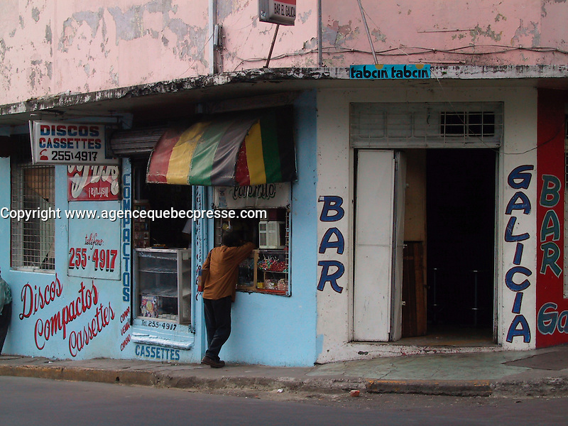 San Jose, COSTA RICA , File Photo  Jan 23, 2001<br /> A Costa Rican stand in front small food stall beside a bar entrance  in downtown San Jose, COSTA RICA on Jan 23rd, 2001