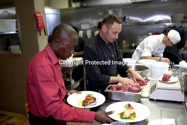 CAPE TOWN, SOUTH AFRICA - MARCH 22: Chef Laurent Deslandes prepares dishes with his staff at bizerca bistro on March 22, 2012 in Cape Town, South Africa (Photo by Per-Anders Pettersson)