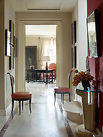 The entry hall is a rich combination of cream that blends with the stone floors, and a warm, earthy shade of terracotta. A pair of Austrian Biedermeier chairs and a circa-1970 travertine demilune console stand in the hallway. A steel armoire and circa-1848 desk in the living room beyond are French.