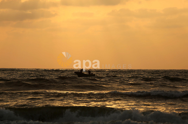 Palestinian fishermen ride their fishing boat in Gaza sea on July 5, 2017. An immediate consequence of the electricity cuts has been suffering for Gazans. A new U.N. report said Gaza gets electricity just four to six hours a day, and 29 million gallons of sewage is flooding into the Mediterranean Sea every day and threatening to overflow into the streets. Photo by Ashraf Amra