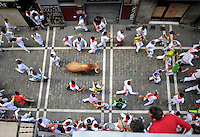 San Fermin, July 2012. Pamplona : Participants run with fighting bulls during a  San Fermin bull run in Pamplona on July 14, 2012. On each day of the San Fermin festival six bulls are released at 8:00 a.m. (0600 GMT) to run from their corral through the narrow, cobbled streets of the old navarre town over an 850-meter (yard) course. Ahead of them are the runners, who try to stay close to the bulls without falling over or being gored. Photo: Ander Gillenea.