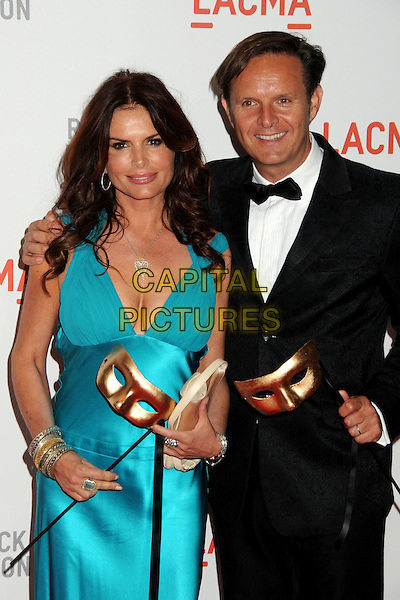 "ROMA DOWNEY & MARK BURNETT.LACMA's ""The Unmasking"" of the Lynda & Stewart Resnick Exhibition Pavilion Opening Gala held at the Los Angeles County Museum of Art, - Los Angeles, California, USA, 25th September 2010..half length blue turquoise dress mask cleavage clutch bag  black tuxedo tux bow tie .CAP/ADM/BP.©Byron Purvis/AdMedia/Capital Pictures."
