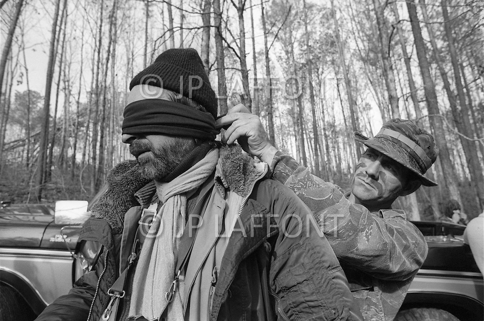 Region of Huntsville, AL - December 6th and 7th 1980<br /> There's a camp of Special Forces of the KKK. <br /> We are a small group of journalists invited to witness their training Deep in a forest of Alabama, bordering Tennessee, training ground for the Ku Klux Klan&rsquo;s secret army. the photographer JP Laffont, blindfolded by a member of the KKK Secret Army.<br /> R&eacute;gion de Huntsville, Alabama. 6 et 7 d&eacute;cembre 1980.<br /> Nous sommes un petit groupe de journalistes invit&eacute;s &agrave; un entra&icirc;nement des troupes arm&eacute;es du Ku Klux Klan. On nous a band&eacute; les yeux (ici JP Laffont)  et nous avons d&ucirc; passer une nuit dans la for&ecirc;t pour assister au petit matin &agrave; un exercice militaire et de tirs d'un groupe arm&eacute; et cagoul&eacute;. On nous a dit que dans cet &eacute;tat ils avaient le droit d'avoir des armes et de s'entra&icirc;ner, non pas &agrave; tuer mais &agrave; d&eacute;fendre la culture de la race blanche.