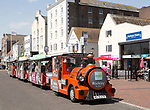 Rockley Rocket land train passing old historic buildings on quayside at Poole harbour, Poole, Dorset, England, UK