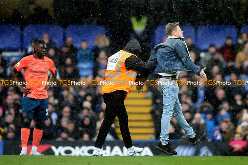 A pitch invader is escorted off the pitch by a Chelsea steward during Chelsea vs Everton, Premier League Football at Stamford Bridge on 8th March 2020