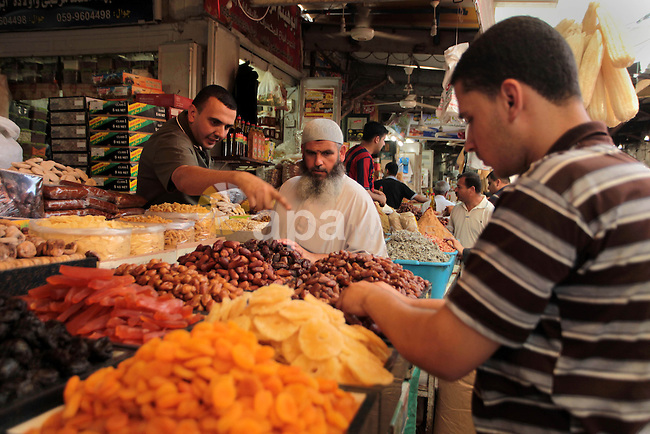 A Palestinian man sells spices in her shop at a market in Gaza City, as Muslims prepare for the upcoming holy fasting month of Ramadan, on June 28, 2014. on the eve of the start of the Muslim holy month of Ramadan. During Ramadan, Muslim believers abstain from eating, drinking, smoking and having sex from dawn until sunset. Ramadan is sacred to Muslims because it is during that month that tradition says the Koran was revealed to the Prophet Mohammed. Photo by Ashraf Amra