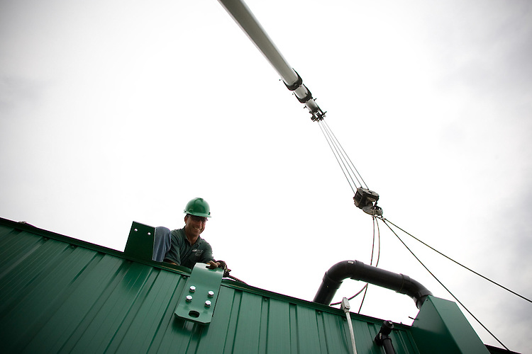 Bill Lawless attaches the Wright Environmental in-vessel composting unit to a crane that will lower the unit into the future Ohio University compost site on Dairy Lane. Photo By: Josh Armstrong