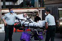 NEW YORK, NY - MAY 7: A man on a stretcher exits Langone Health Hospital in New York alongside two medical workers as three JetBlue jets honor health workers with a special low-altitude flight over Manhattan during the COVID-19 pandemic on May 7. 2020 in New York, NY. COVID-19 has spread to most countries in the world, claiming more than 270,000 lives and more than 3.9 million people have been infected. (Photo by Andres Mesa / VIEWpress via Getty Images)