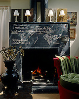 A blackboard-faced fireplace is covered in notes and quotations in this living room