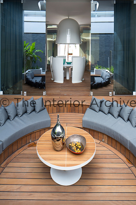 Mirrored doors open from the dining area at the Villa Bianca in Iniala onto a teak-decked terrace featuring a sunken seating area