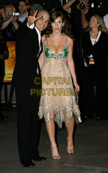 ANNA FRIEL & KUNO BECKER.At The Goal Film Premiere held at the Odeon Cinema,.Leicestre Square,.London, 15th September 2005.full length cream sparkly chiffon layer dress green butterfly detail fake fur wrap gold handbag purse black suit peace sign hand fingers.Ref: AH.www.capitalpictures.com.sales@capitalpictures.com.© Capital Pictures.