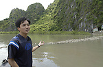 Halong-Vietnam, Ha Long - Viet Nam - 22 July 2005---Mr. Tran, a local UNV (United Nations Volunteer), points at and explains the project area of the Youth Mangrove Forest on Dau Go island, an activity of the Youth Union at Halong Bay, a UNESCO World Natural Heritage Site---landscape, nature, portrait---Photo: Horst Wagner/eup-images