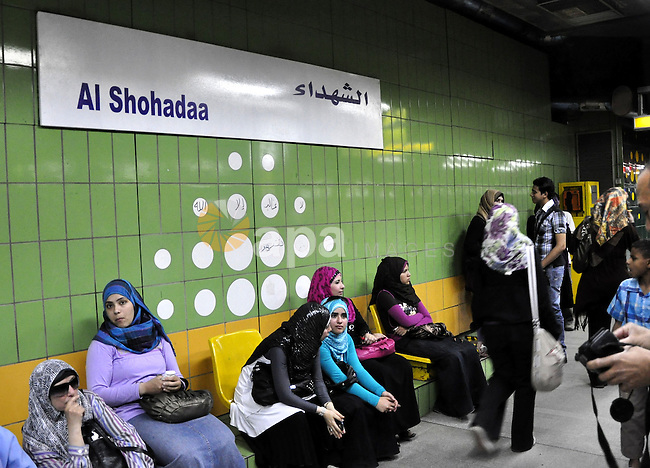 """Egyptian women wait at a metro station under a placard holding the name Al Shohadaa """"the Martyrs"""" in Arabic and English in Cairo, Egypt  on May 03, 2011. Al Shohadaa is the new name of the metro which called in the past in the name of the ousted President Mubarak. Photo by Ahmed Asad"""