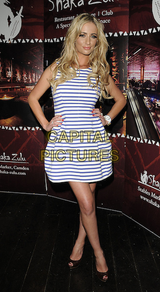 Chantelle Houghton.Shaka Zulu 1st birthday party, Shaka Zulu bar & restaurant, the Stables Market, Chalk Farm Rd., London, England..August 4th, 2011.full length white blue sleeveless striped stripes dress black hands on hips peep toe shoes.CAP/CAN.©Can Nguyen/Capital Pictures.