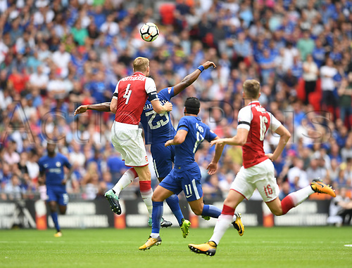 August 6th 2017, Wembley Stadium, London, England; FA Community Shield Final; Arsenal versus Chelsea; Per Mertesacker of Arsenal heads the ball clear of goal challenged by Michy Batshuayi of Chelsea