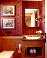 The walls of the small bathroom are half-panelled and decorated with red patterned wallpaper