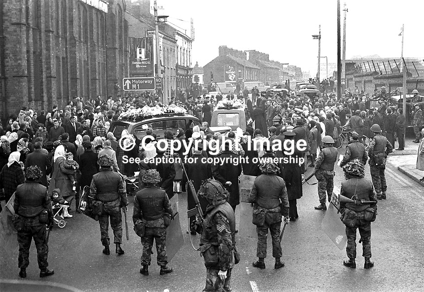 Funerals of four Provisional IRA members killed in car explosion on the Knock Dual Carriageway, Belfast, presumably on their way to a bombing target. The dead men were Gerard Steele, Gerard Bell, Joseph Magee and Robert Dorrian, all from the Short Strand area of Belfast, from where the funeral went to Milltown Cemetry. Members of the RUC and British Army keep a watchful eye. NI Troubles. Ref: 19720223003.<br />