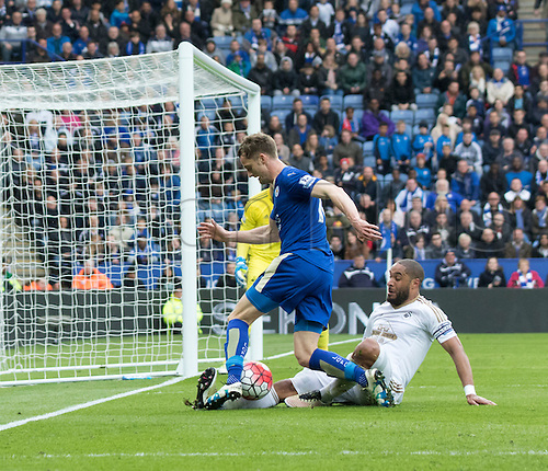 24.04.2016. King Power Stadium, Leicester, England. Barclays Premier League. Leicester versus Swansea.  Swansea City defender Ashley Williams (C) comes in hard on Leicester City midfielder Andy King to clear the ball from the goal area.