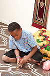 8 year old boy sitting on floor counting sorting coins piggy bank nearby vertical