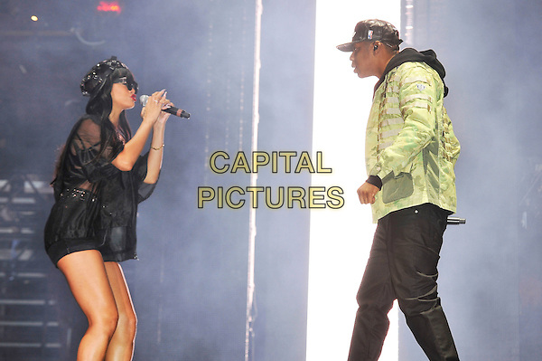"Rihanna (Robyn Rihanna Fenty) & Jay-Z (Shawn Corey Carter).Perform ""Run This Town' at the BBC Radio 1 Hackney Weekend, Hackney Marshes, London, England, UK, 23rd June 2012..music concert festival gig performing live on stage half length singing microphone cap hat  black round sunglasses shorts bra crop top belt shirt jacket high waisted bondage green jacket duet hoodie .CAP/MAR.© Martin Harris/Capital Pictures."