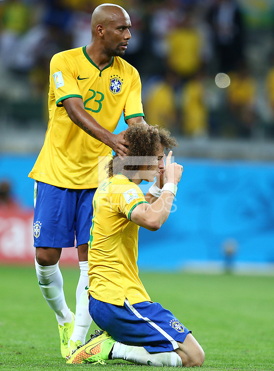 Maicon of Brazil consoles a dejected David Luiz as he prays at full time