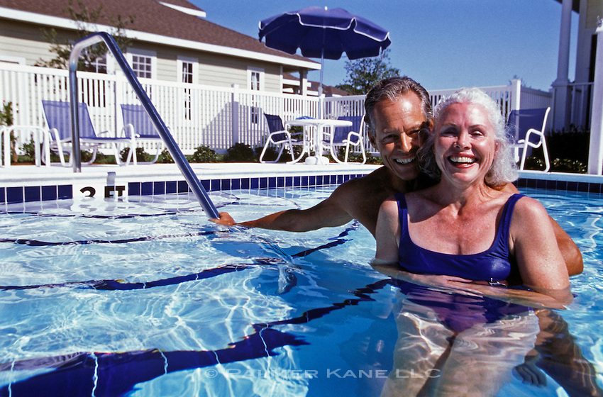 Portrait of retired couple at home in pool
