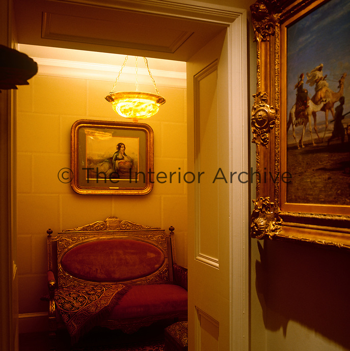 The hall is furnished with a gilded sofa against a trompe l'oeil stone wall