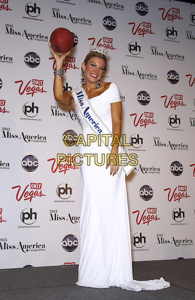 Miss America Mallory Hagan.Miss New York Mallory Hagan holds her first press conference as Miss America 2013 at Planet Hollywood Casino Resort, Las Vegas, Nevada, USA, .12th January 2113..full length white one shoulder dress sash long maxi  crown tiara holding american football funny .CAP/ADM/MJT.© MJT/AdMedia/Capital Pictures.