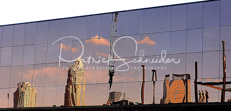 The Charlotte skyline and construction workers are reflected in the windows of the Moorehead Corporate Plaza, on Moorehead Street, in Charlotte, N.C.  The construction works were placing the steel beams on a new office building on East Moorehead Street.