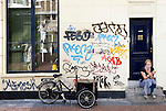 AMSTERDAM - The NETHERLANDS - 09 September 2012 -- Graffiti, bicycle with a young woman smoking. -- PHOTO: Juha ROININEN /  EUP-IMAGES