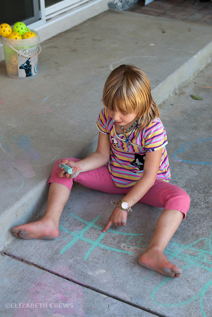Berkeley CA Girl, seven, setting up chalked diagram for game of tick-tack-toe  MR