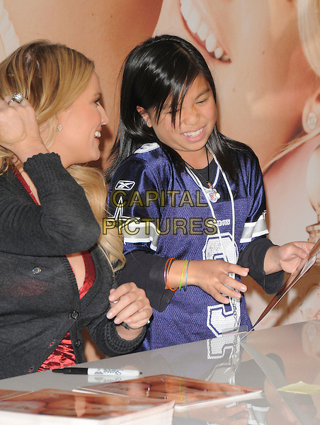"JESSICA SIMPSON.launches ""Fancy"" her new fragrance at Macy's South Coast Plaza in Costa Mesa, California, USA, .December 13th 2008.                                                                    .half length red satin silk cleavage  grey gray cardigan hand touching hair fan sitting table pen signing .CAP/DVS.©Debbie VanStory/Capital Pictures"