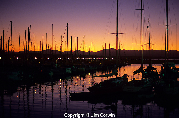 Shilshole Marina and Puget Sound with Olympic Mountains and power boats and sailboats silhouetted at sunset Seatttle Washington State USA.