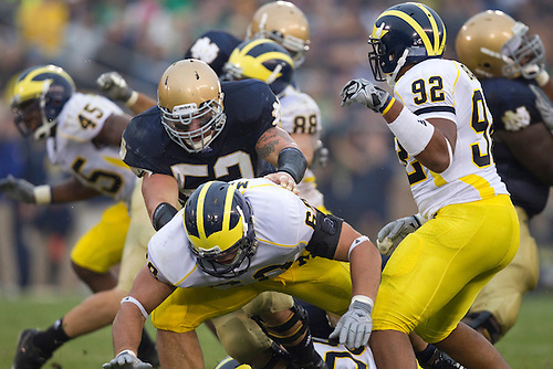 Notre Dame center Braxston Cave (#52) blocks Michigan defensive tackle Alex Schwab (#68) during NCAA football game between the Notre Dame Fighting Irish and the Michigan Wolverines.  Michigan defeated Notre Dame 28-24 in game at Notre Dame Stadium in South Bend, Indiana.