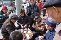 People playing cards in the street..Shanghai, February 2006.