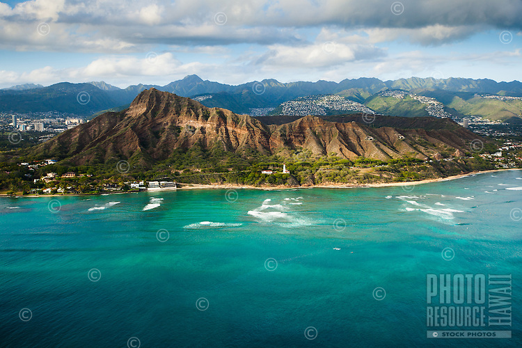 A patch of sunlight streaks across the side of Diamond Head in this aerial shot, with the Ko'olau Mountains in the background.