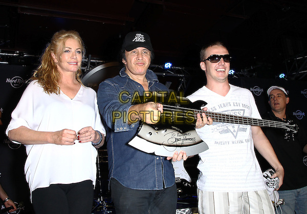 Shannon Tweed, Gene Simmons.Hard Rock Cafe Las Vegas Strip celebrates Gene Simmons. A fan wins a drawing for a signed Gene Simmons bass and Gene Simmons signs a bass he will play in concert tonight and then donate to the HRC permanent collection, Las Vegas, Nevada, USA..August 11th, 2012.half length black baseball cap hat jeans denim jean shirt white top couple axe guitar.CAP/ADM/MJT.© MJT/AdMedia/Capital Pictures.