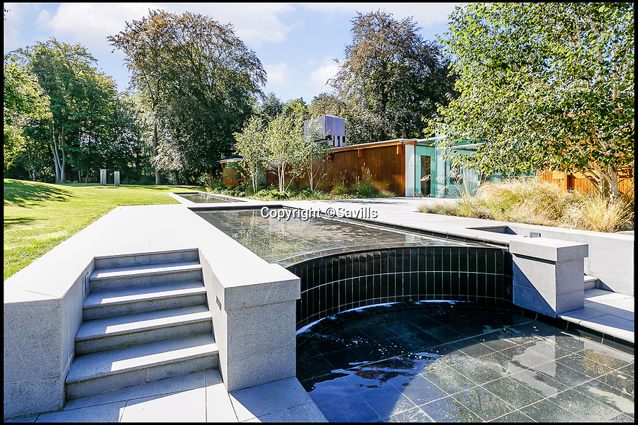 BNPS.co.uk (01202 558833)<br /> Pic: Savills/BNPS<br /> <br /> Stunning water feature ...<br /> <br /> Perfect home for a Bond villan...designed by a Bond villan!<br /> <br /> This stunning 1960's modernist masterpiece near Windlesham in Surrey was actually designed by Hungarian architect Erno Goldfinger - who bizarrely author Ian Fleming had based one of his most notorious James Bond villans on.<br /> <br /> Fleming was furious with Goldfinger after the architect had demolished his Hampstead cottage to make way for a modernist development before the war.<br /> <br /> But at £3 million you may need your own gold reserves to afford the stunning grade two listed home, and with 4 acres of grounds an 'Oddjob' man may come in handy to look after it.