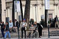 Anziano sulla sedia a rotelle in via dei Fori Imperiali aiutato da alcune persone alla fermata degli autobus.Elder wheelchair in via dei Fori Imperiali helped by some people