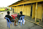 "Two men relax at a table at a brothel, as a woman walks to her room in Kampong Chhnang Province, Cambodia.  When Randa Lee first returned to her country, she agonized over the women trapped in such a life. ""A lot of girls had been kidnapped,"" she says. ""A lot of parents were so sick they sold their daughters to be prostitutes.  Or sometimes the girls just did it to get money...It was a shame on the country."".."